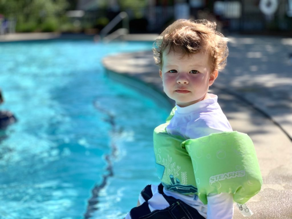 baby with a life vest sitting on the edge of the pool