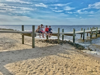 kids sitting on a river pier