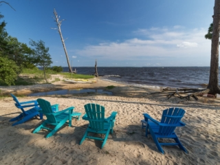 2 dark blue and 2 teal adirondack chairs placed on the sandy riverfront beach overlooking the river