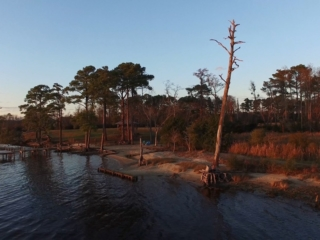 an aerial view of the riverfront beach and dock at dusk