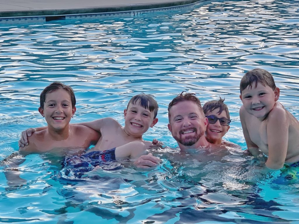 a dad and four boys laughing and swimming in the pool
