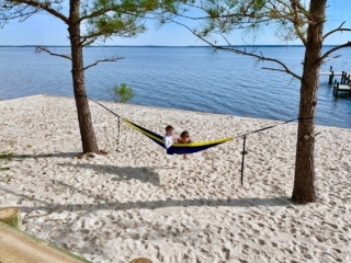 two kids sit in a hammock, hung between two tress, on a riverfront beach overlooking the neuse river
