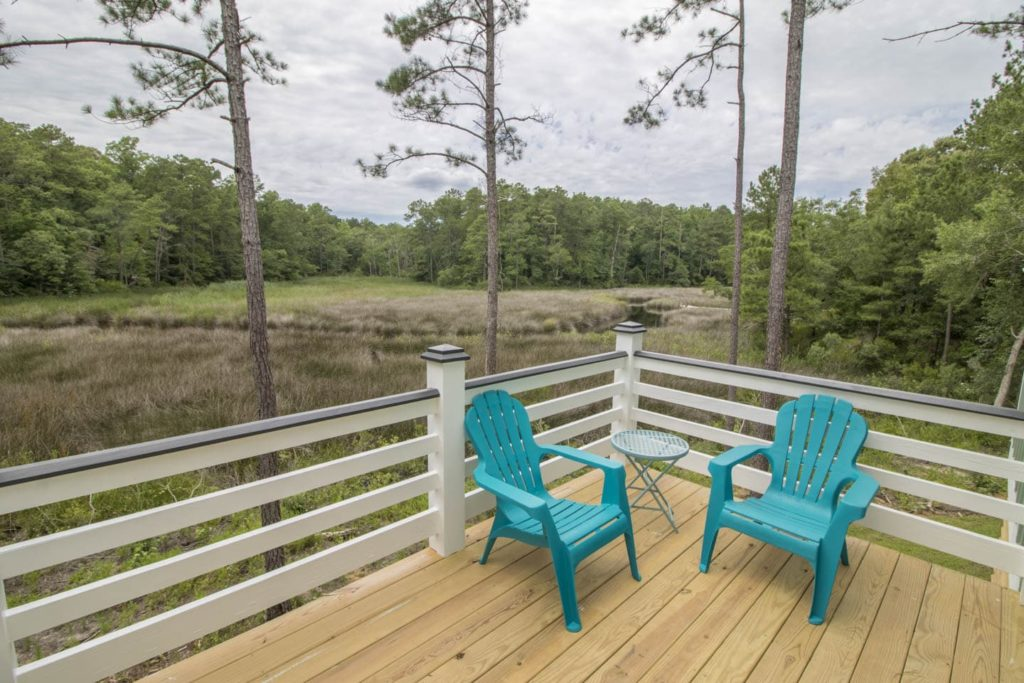 The 2 bed 1 bath Reelin' In the Years Cottage has 2 porches, modern amenities and a marsh view overlooking Mill Creek.