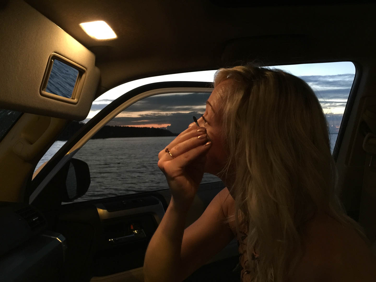Girl applying eyeliner while riding on a ferry.