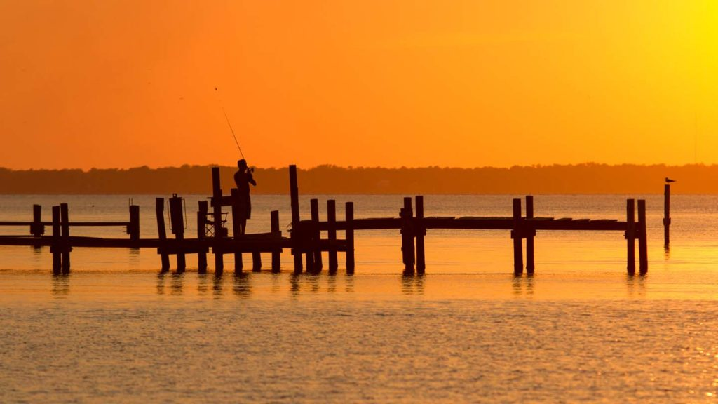 Fisherman casting into the Neuse River at sunset in Pamlico County, NC.
