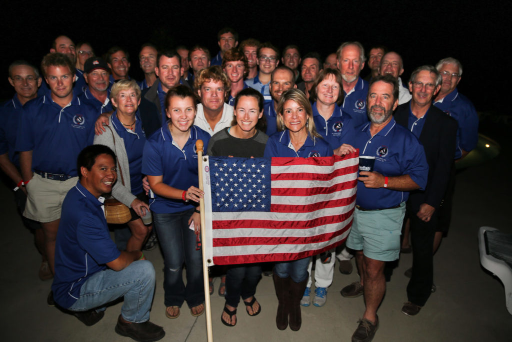 The sunfish worlds team holds an american flag and smiles for the camera