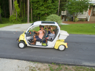 a family of four rides their yellow gold cart on the way to the clubhouse, dog in tow