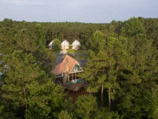 aerial view of the outfitter's center with three cottages and woods in the background