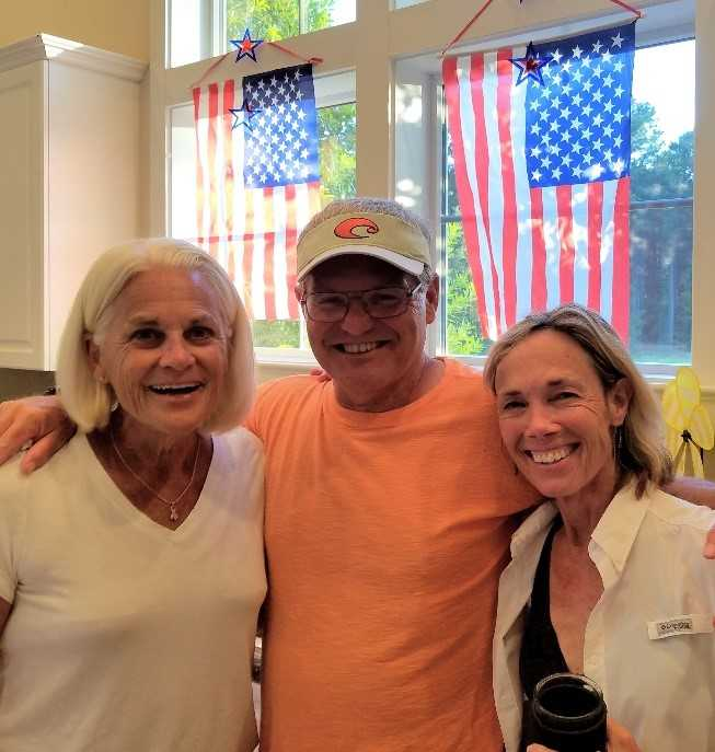 three neighbors smile at the camera at a 4th of July party