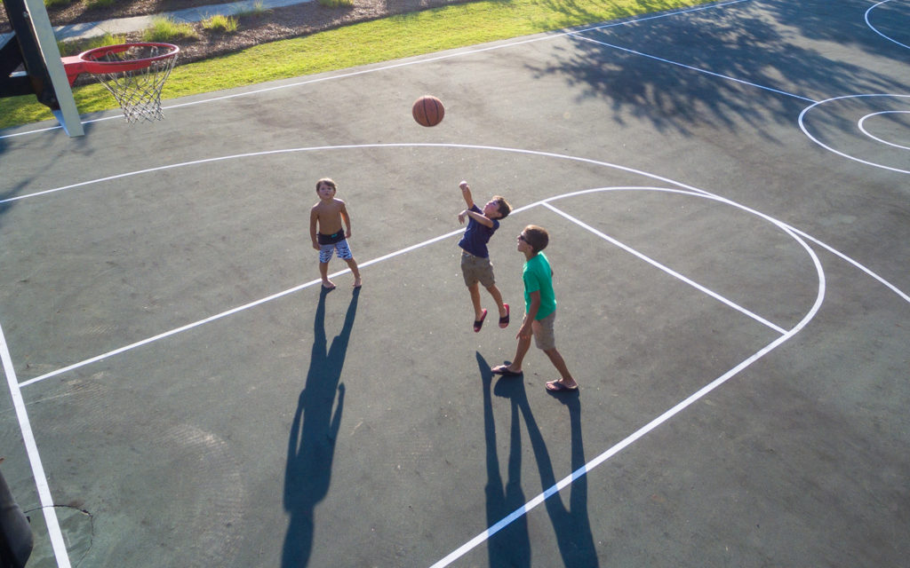 three kids playing basketball on the Arlington place basketball court