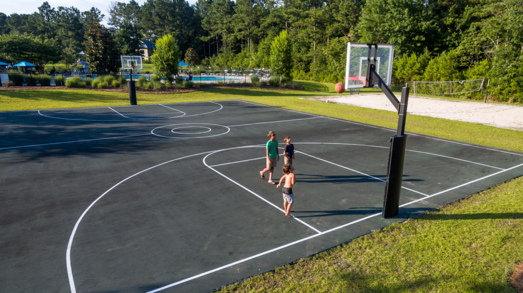 three boys play basketball on the court at Arlington Place