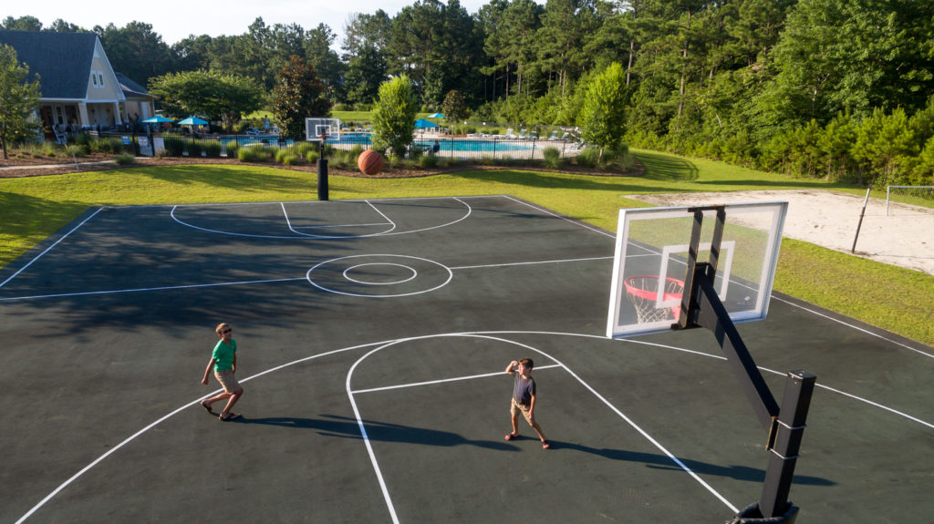two boys playing on a basketball court