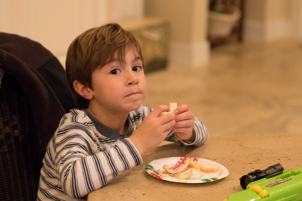 a boy looks at the camera while eating a plate of apple slices