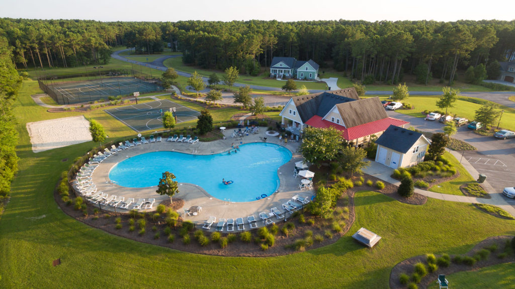 aerial view of the pool, clubhouse, and sports courts