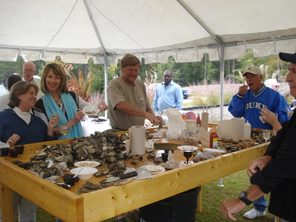 Neighbors gather around the oyster table to chow down