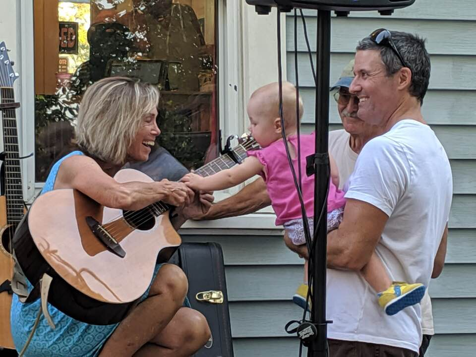 father holds a baby reaching for her grandma's guitar