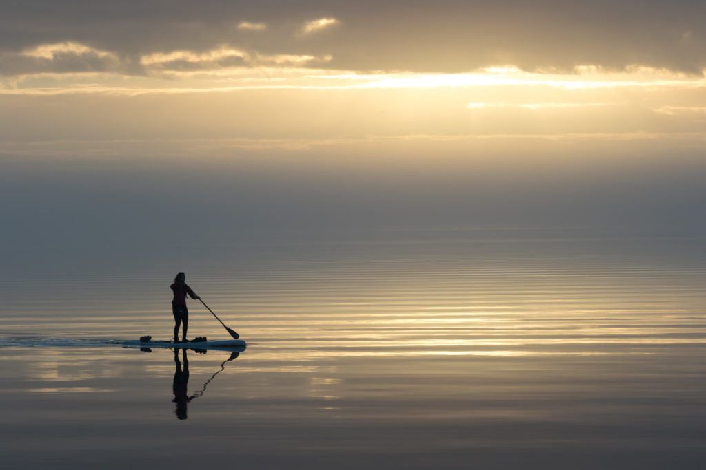 A paddle boarder enjoys a sunrise on the Neuse River. Photo by William Hughes Conkwright.