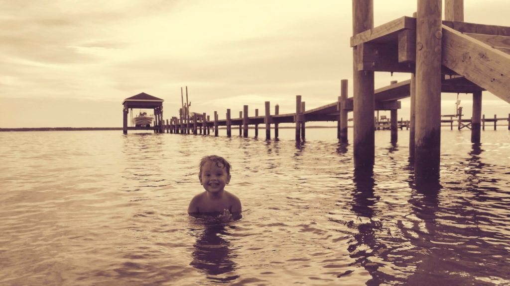 Little boy playing in the water near a dock.