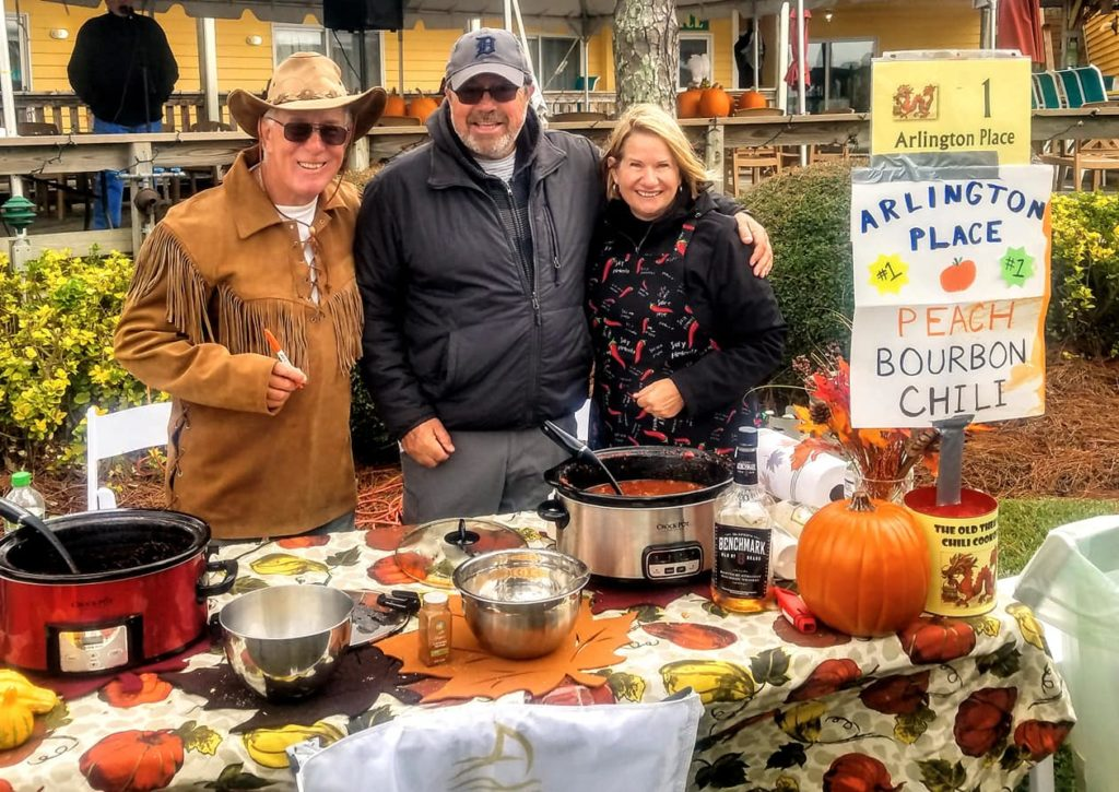 three neighbors in front of the Arlington Place chili booth smile for the camera