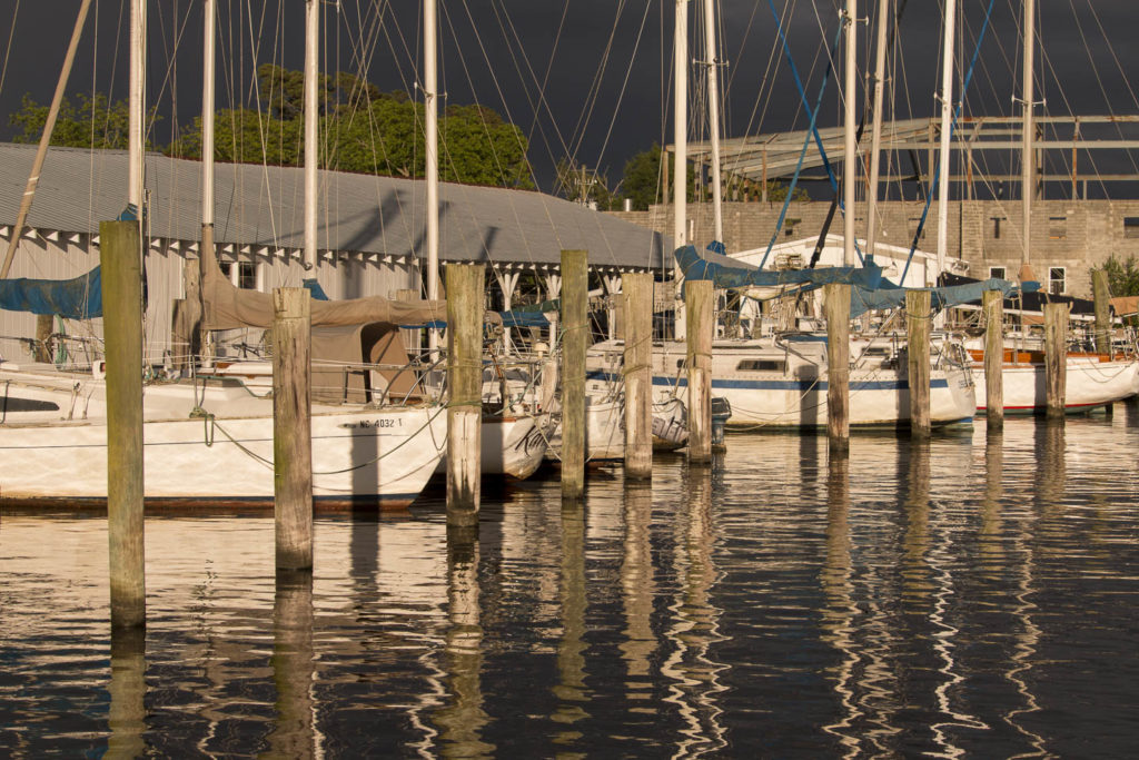 Sailboats reflecting in the water at the marina in Oriental, NC.