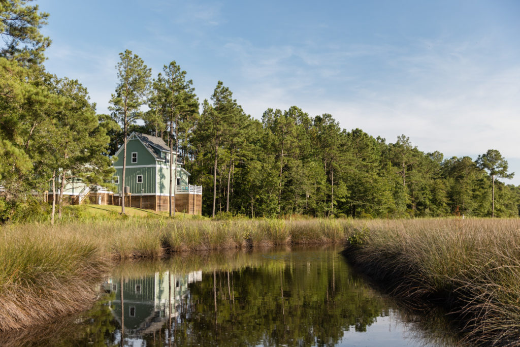 One of the Outfitters Cottages at Arlington Place reflecting off of Mill Creek.