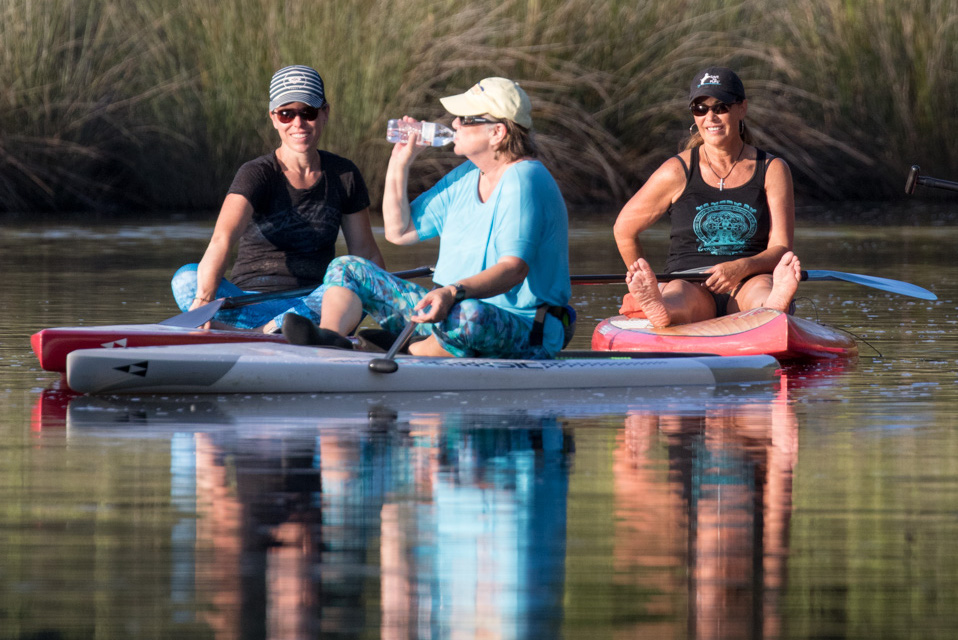 Three ladies relaxing on paddle boards on Mill Creek in Arlington Place.