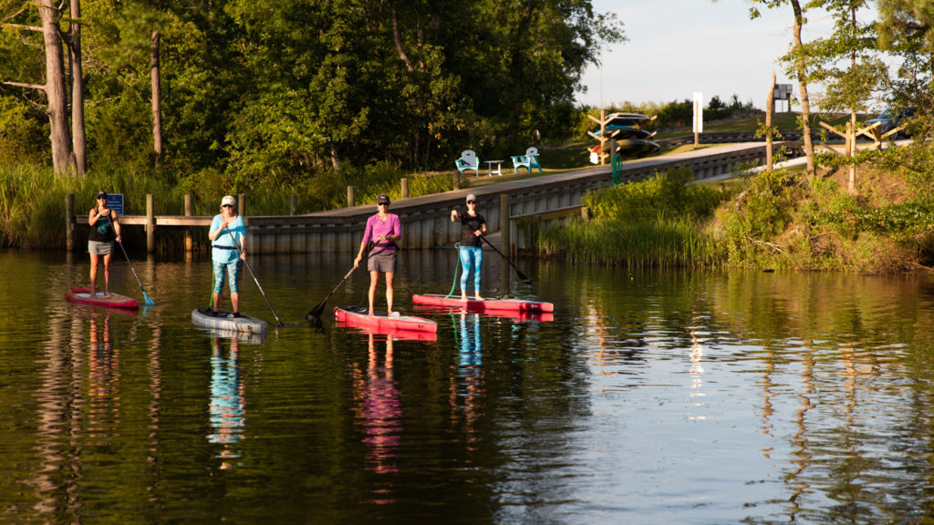 Three ladies paddling by the community boat ramp on Mill Creek at Arlington Place.