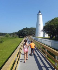 Kids walking down boardwalk to Ocracoke lighthouse.