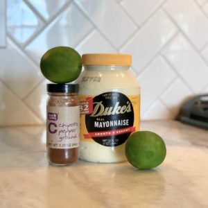 Mayonnaise and limes on a counter top.