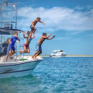 Kids jumping from the boat.