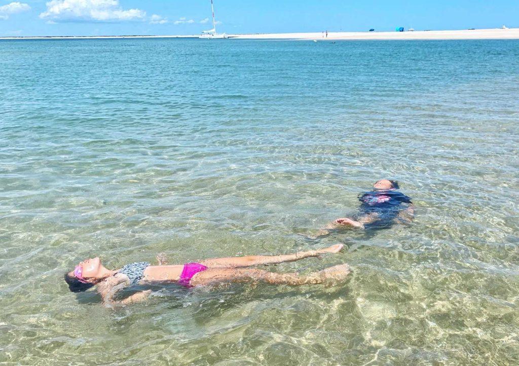 Kids floating in wading pool water.