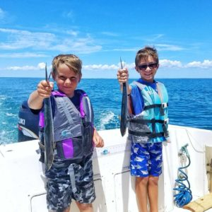 Kids with Spanish Mackerel fish.