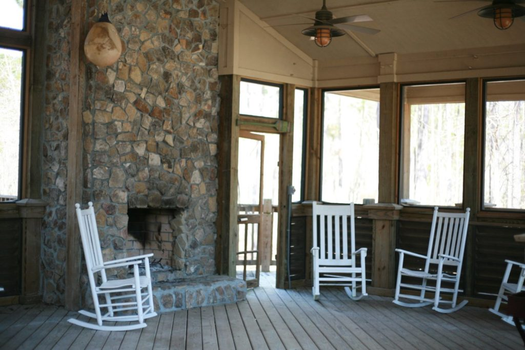 interior of the outfitters center with white rocking chairs and a large stone fireplace