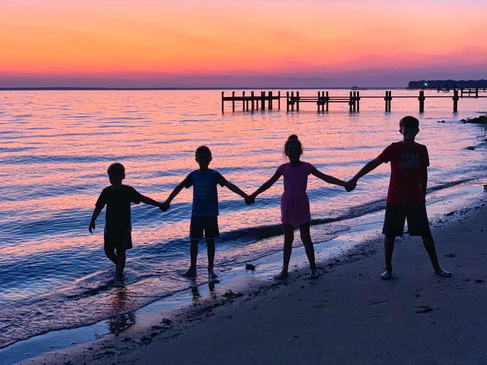 kids holding hands on the beach at sunset