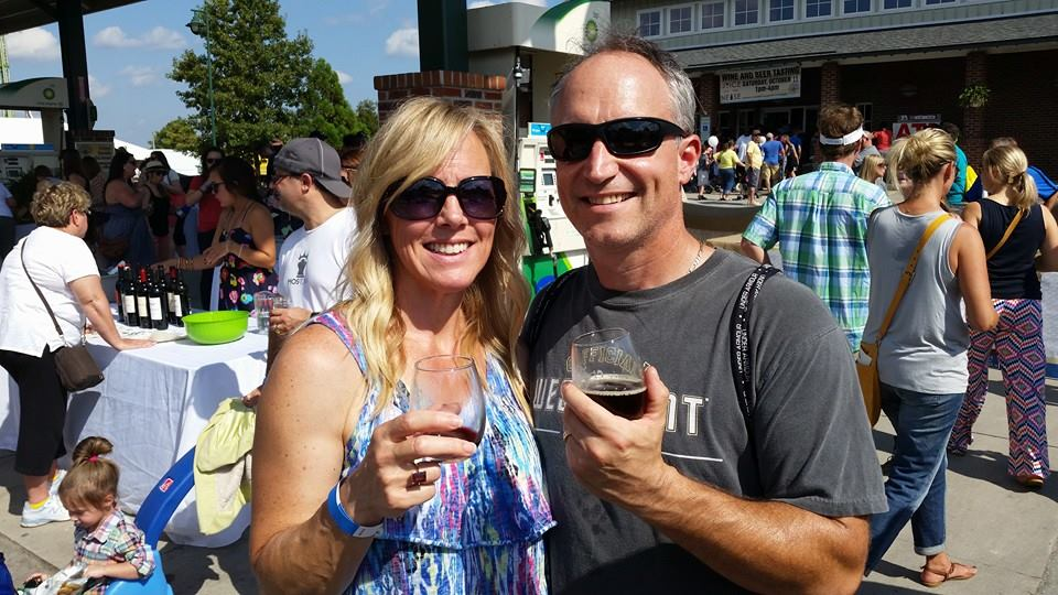 two neighbors hold glasses of wine while enjoying the mumfest in downtown new bern