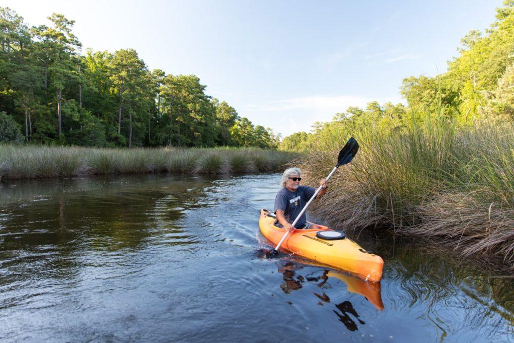 Man paddling a kayak down a creek.