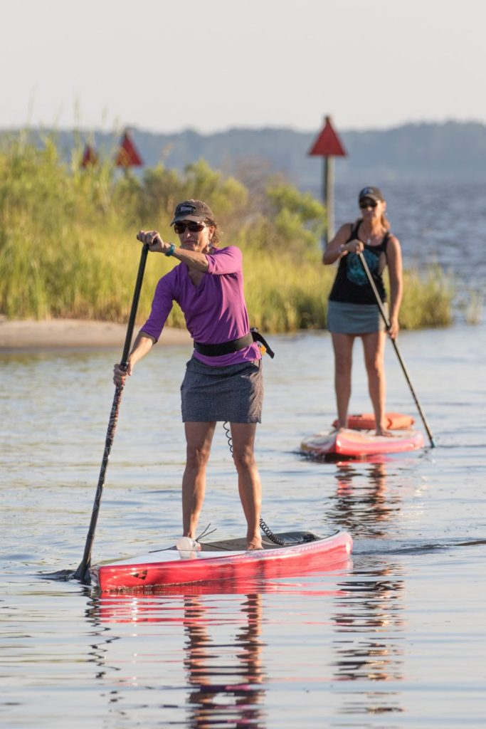 two women paddle boarding into the creek
