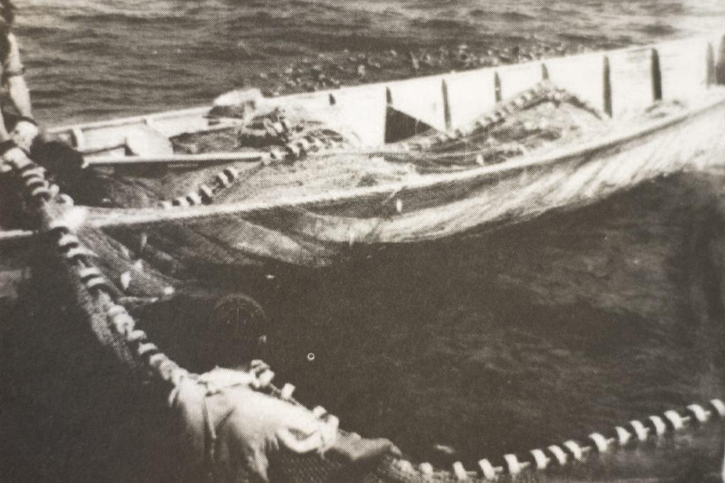 Historic photograph of two men net fishing.